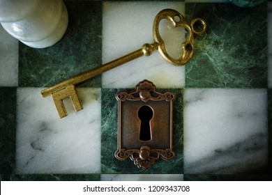 Gold key with antique lock on a chess board