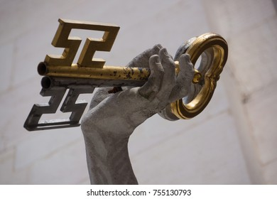 Gold key, close up, held up by a carved stone hand in Austria.