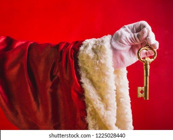 Gold key in hand of Santa Claus on a red background.