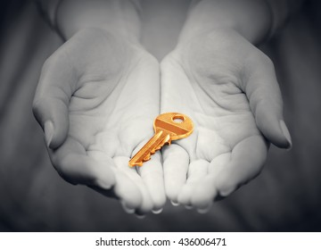 Gold key in woman's hand in gesture of giving. Strong spotlight. Concept of success in live, business solution, real estate industry etc.