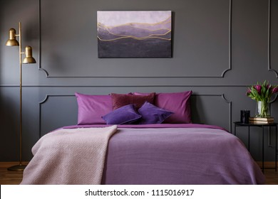 Gold lamp next to purple bed against grey wall with molding and poster in woman's bedroom interior