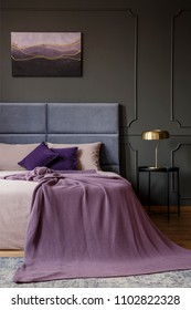 Gold lamp on black table next to bed with pink blanket in pastel bedroom interior with poster