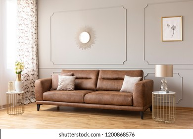 Gold lamp on table next to leather settee in grey living room interior with poster and mirror. Real photo