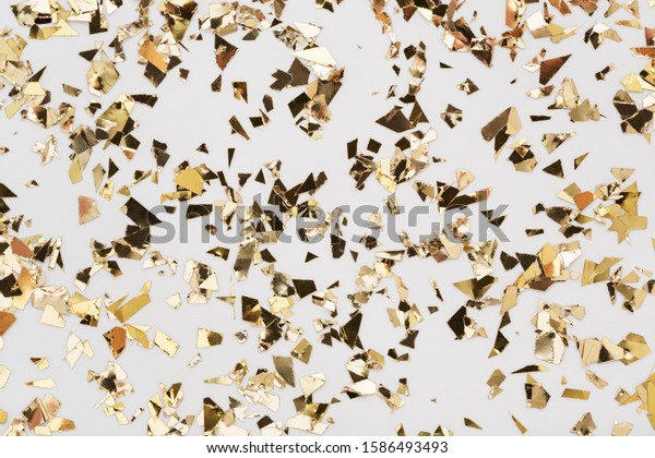 Gold leaf confetti on white background. Festive, party or holiday glitter backdrop. Flat-lay, close-up.
