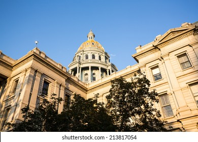 The gold leaf covered dome of the State Capitol Dome in Denver Colorado shortly after sunrise