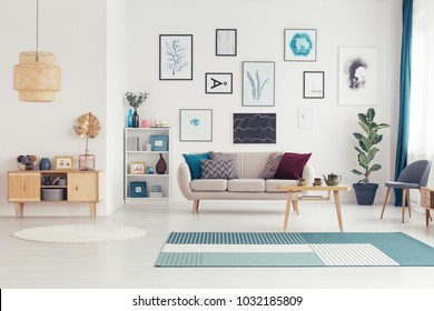 Gold leaf on wooden cupboard in spacious living room interior with table on blue carpet near settee