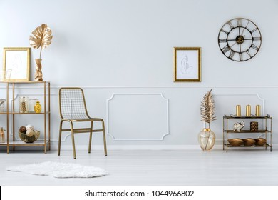 Gold leaves and chair against white molding wall with poster in luxurious living room interior