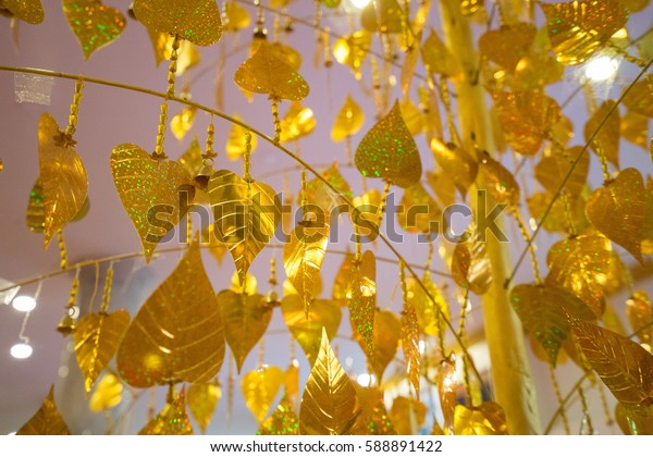 Gold leaves hanging on golden tree, decorating yellow pho leaf, symbol of buddhism religion
