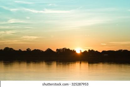 Gold light on sun set with light on the river.Idyllic Wallpaper Setting Sun.