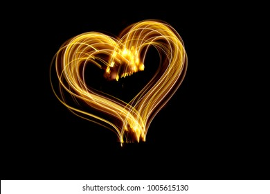 Gold light painting photography, long exposure, outline heart shape, metallic effect against a black background. Love concept