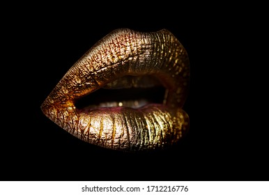 Gold lips. Gold Paint from the lips. Golden lips on beautiful model girls mouth. Make-up. Beauty makeup close up. Golden make up in lips. Gold concept