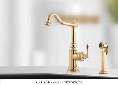 Goldener Luxus-Wasserhahn mit dem kleinen Hebel in der Küche.Stilvolles Design für den Haushalt.Shiny-Kran in Nahaufnahme.Goldenes Waschbecken als Küchenausstattung. Makrofoto von hoher Qualität. Foto von Wasserhahn.