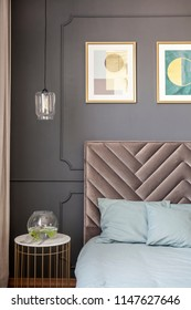 Gold and marble end table with decorative plant standing next to bed with soft bedhead and light blue bedclothes in grey room interior with posters on the wall
