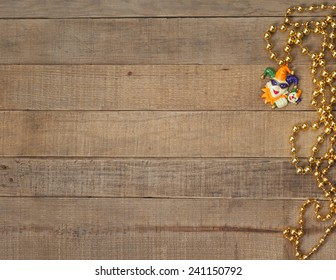 Gold Mardi Gras Beads with Court Jester on Rustic Brown Wood Background with room or space for copy, text, your words.  Above looking down horizontal