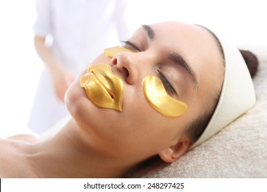 Gold mask collagen hydrogel, cosmetic surgery . Cosmetic procedure, the woman's face with gold flakes under the eyes and on the lips