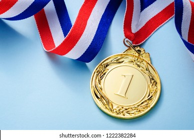 Gold medal 1 place with a ribbon on a light blue background, the concept of victory or success
