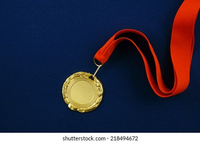 Gold medal with red ribbon on blue velveteen with room for text