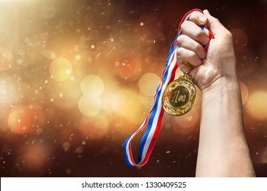 Gold medal with  ribbon  in hand on  background
