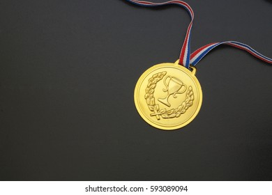 Gold medal with ribbon on black board