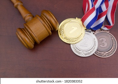 Gold medal, silver medal, bronze medal and wooden judge gavel, arbitration sport court concept.