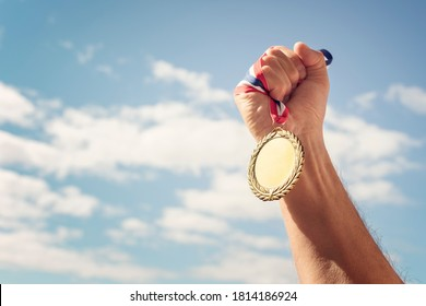 Goldener Medaillengewinner in der Hand auf blauem Hintergrund