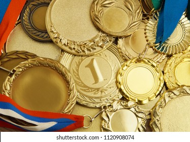 A lot of gold medals with ribbons
