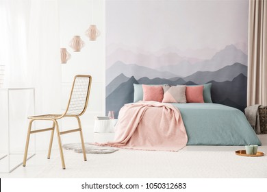 Gold, metal chair in a soft, bright bedroom interior with a mountains wallpaper, pastel pink and blue bedding and pillows