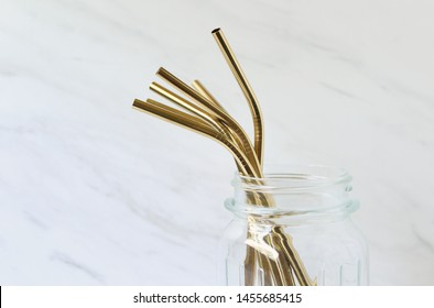 Gold metal reusable straws in glass jar. Environmental conservation concept. Copy space.