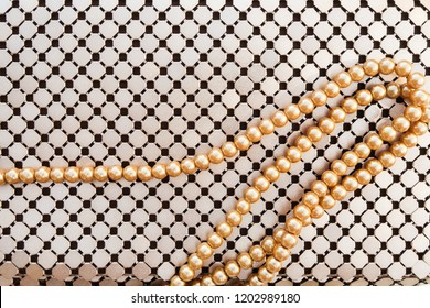 Gold metallic bag and gold pearl necklace pattern texture background