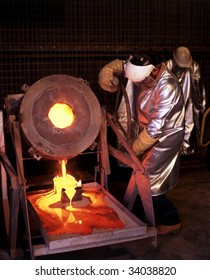 Gold mine worker pours molten Gold into ingot mold