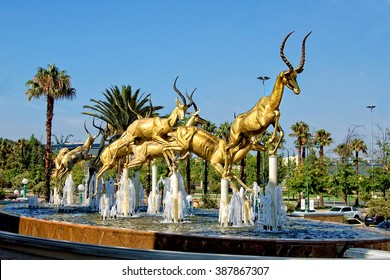 Gold. Mining industry of South Africa. Amazing golden springboks jump in a fountain with blue sky in the background. Johannesburg. Gold Reef City. South Africa - December 21, 2013