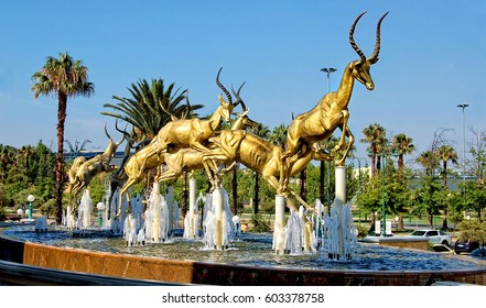 Gold. Mining industry of South Africa. Amazing golden springboks jump in a fountain with blue sky in background. Johannesburg Gold Reef City. South Africa - December 21, 2013