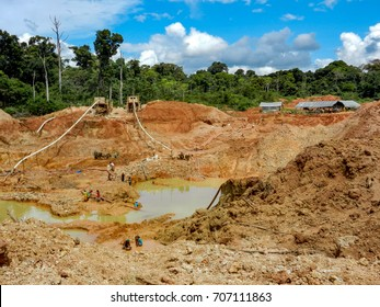 Gold mining place in Guyana, local amerindians clear workspace from stones and check it for gold nuggets. Amazon and Essequibo basin deforestation. Guyana, Brazil, Venezuela gold mining exploration.