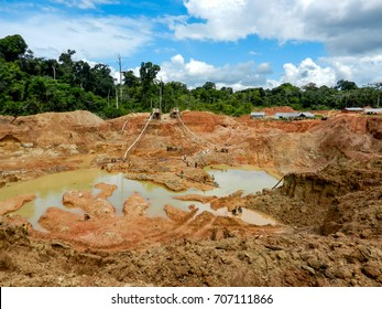 Gold mining place in Guyana, local amerindians clear workspace from stones and check it for gold nuggets. Amazon and Essequibo basin deforestation. Guyana, Brazil, Venezuela gold mining deforestation.