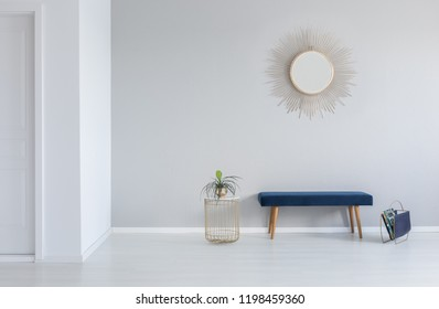 Gold mirror on the wall above blue bench in minimal empty entrance hall interior with plant. Real photo