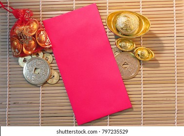 """Gold and money coin on red pocket """" Ang Pao"""" with background wood plate."""