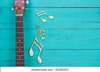 Gold musical notes by neck of guitar with antique rustic teal blue wooden background