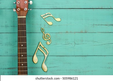Gold musical notes by neck of guitar with antique rustic mint green wood background; green copy space