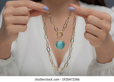 Gold necklace with blue stone on hand of lady with blue nail polish in white clothes.