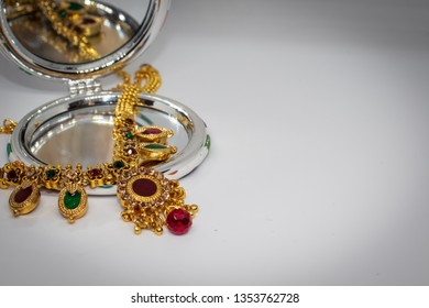 gold necklace with green and red stones placed over a mirror.isolated in white background.