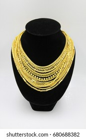 Gold necklace. Many chains gold necklace. Gold necklace on necklace display stand. Gold necklaces on Black mannequin.