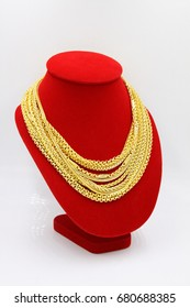 Gold necklace. Many chains gold necklace. Gold necklace on necklace display stand. Gold necklaces on red mannequin.