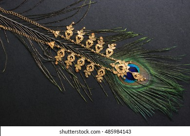 Gold necklace on peacock feather. Black background. Conceptual wedding photography.