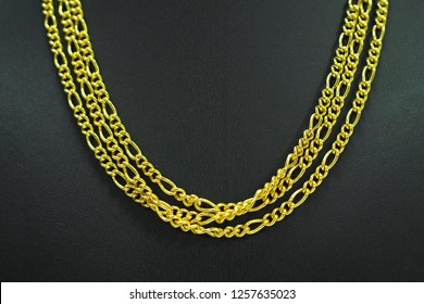 Gold necklaces on necklace display stand.
