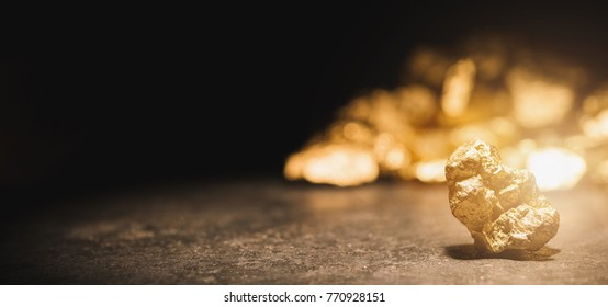 gold nugget in front of a mound of gold