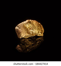 Gold nugget isolated on black background.