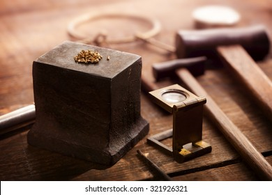 Gold nuggets on a old anvil, with tools in background. intentionally shot in nostalgic tone. Shallow depth of field.