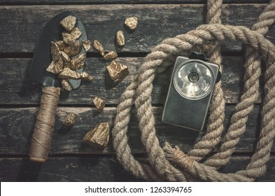 Gold nuggets on the spade, rope and flashlight on the aged wooden table background. Treasure hunter or goldminer concept.