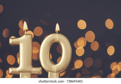 Gold number 10 celebration candle against blurred light background