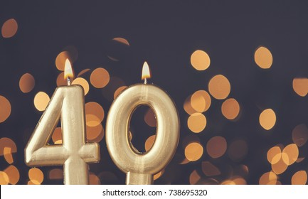 Gold number 40 celebration candle against blurred light background